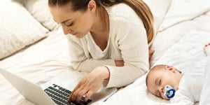 Mother searching for information online while baby sleeps